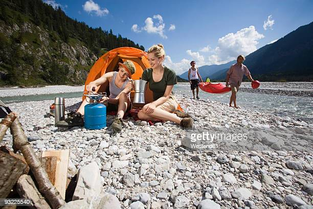 Germany, Bavaria, Toelzer Land, Friends camping beside river