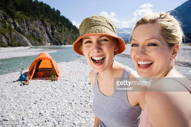 Germany, Bavaria, Toelzer Land, Two women camping by river, laughing, portrait, close-up