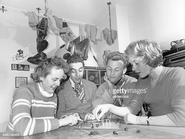 Germany Bavaria two couples playing ludo during cottage holiday