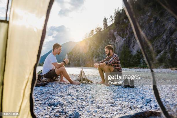 Germany, Bavaria, two hikers camping on gravel bank in the evening