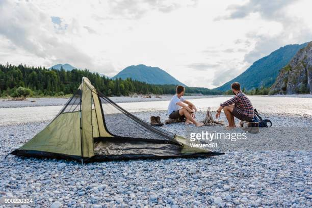 germany, bavaria, two hikers camping on gravel bank looking at view - fiume isar foto e immagini stock