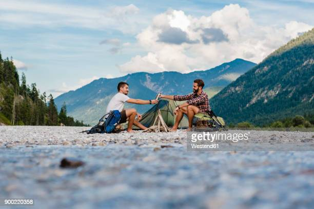 germany, bavaria, two hikers camping on gravel bank - flussufer stock-fotos und bilder