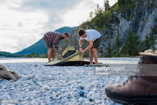 Germany, Bavaria, two hikers putting up tent on gravel bank
