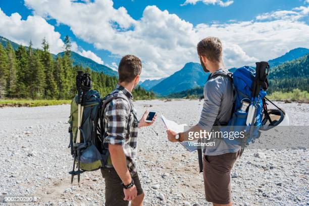 germany, bavaria, two hikers standing in dry creek bed orientating with cell phone and map - karte navigationsinstrument stock-fotos und bilder