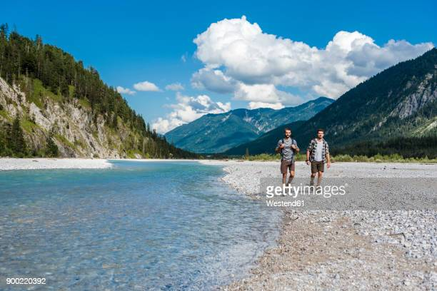 germany, bavaria, two hikers walking at riverside - flussufer stock-fotos und bilder
