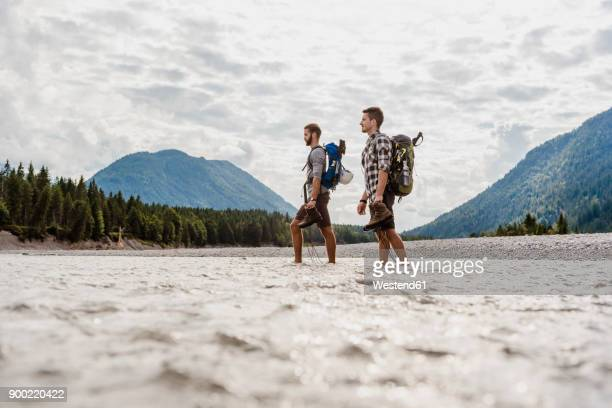 germany, bavaria, two hikers with backpacks crossing isar river - wading stock pictures, royalty-free photos & images