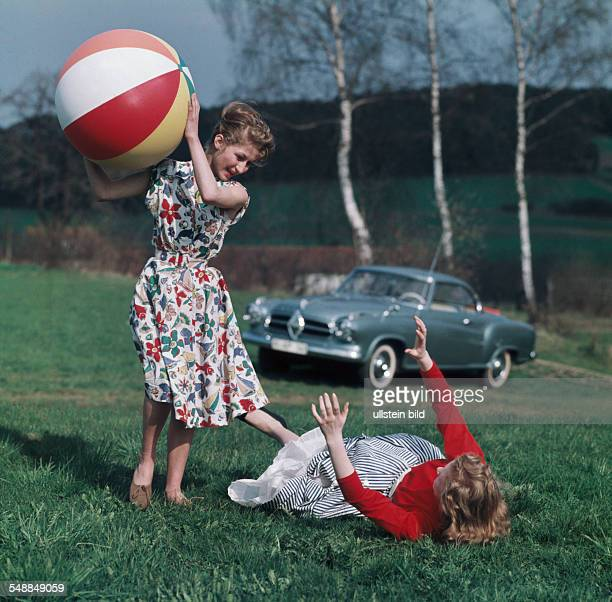 Germany Bavaria two young women are playing with a beach ball on a meadow in the background a Borgward Isabella coupe 1950s