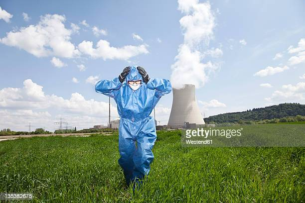 Germany, Bavaria, Unterahrain, Man with protective workwear walking in field at AKW Isar