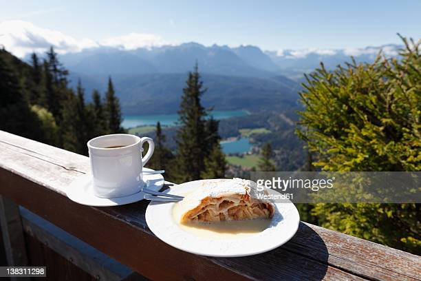 Germany, Bavaria, Upper Bavaria, Apple strudel and coffee cup on fence with mountains in background