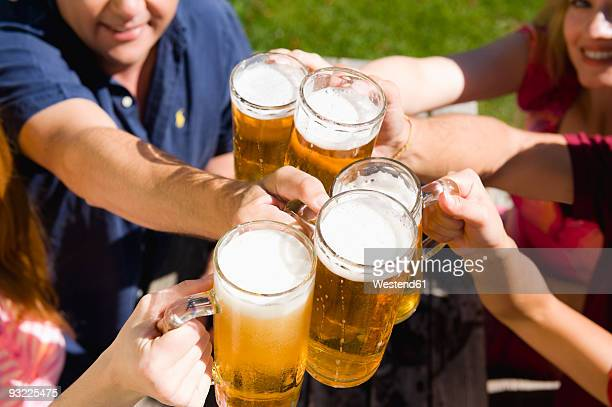 Germany, Bavaria, Upper Bavaria, group of friends toasting with beer, elevated view