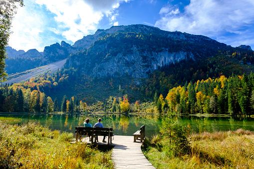 Germany, Bavaria, Upper Bavaria, Chiemgau, Inzell, Frillensee, hikers sitting on bench in autumn - gettyimageskorea