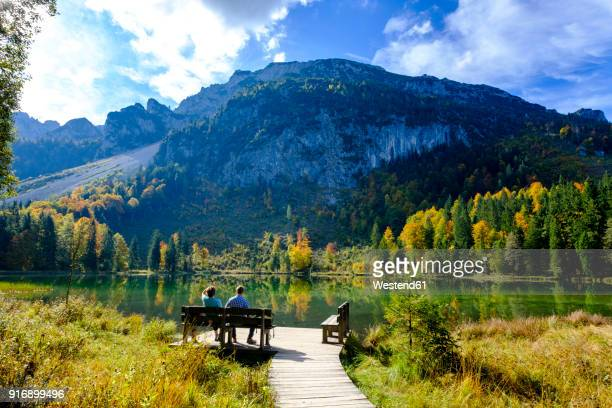 Germany, Bavaria, Upper Bavaria, Chiemgau, Inzell, Frillensee, hikers sitting on bench in autumn