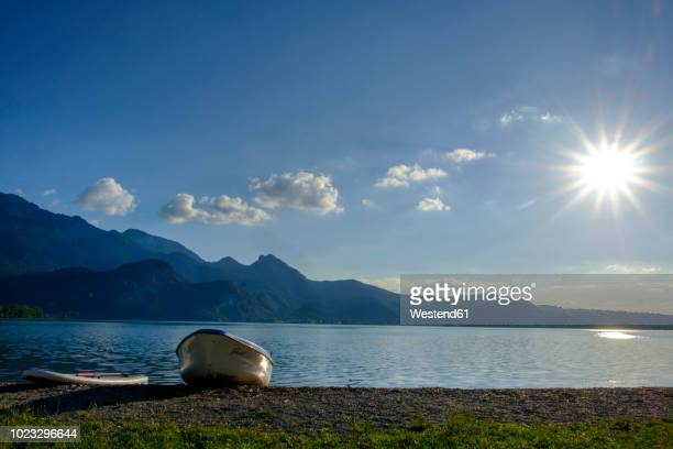 Germany, Bavaria, Upper Bavaria, Heimgarten, Kochelsee, boat and paddleboard at lakeshore against the sun