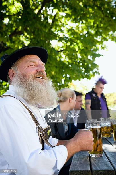 Germany, Bavaria, Upper Bavaria, Man in traditional costume holding beer stein, portrait