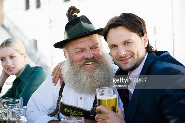 germany, bavaria, upper bavaria, man in traditional cosume and businessman in beer garden, smiling, portrait - レーダーホーゼン ストックフォトと画像