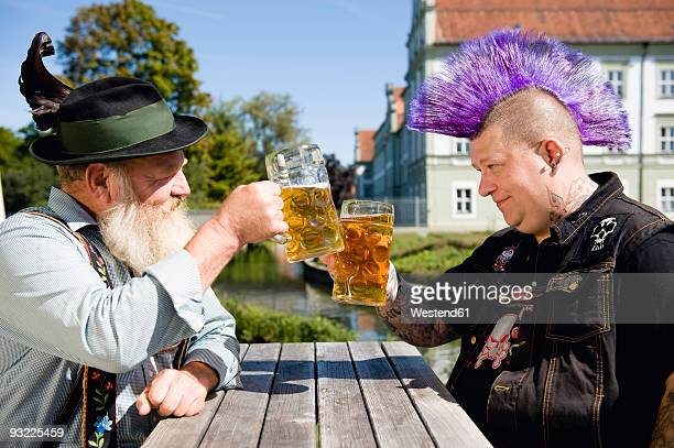 germany, bavaria, upper bavaria, man with mohawk hairstyle and bavarian man holding beer stein glasses - gegensatz stock-fotos und bilder