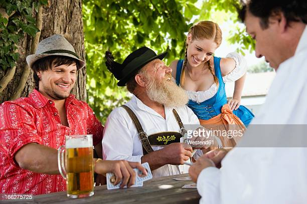 Germany, Bavaria, Mature man with younger friends playing cards in beer garden