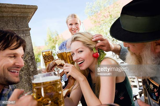 Germany, Bavaria, Upper Bavaria, People in beer garden, waitress in background