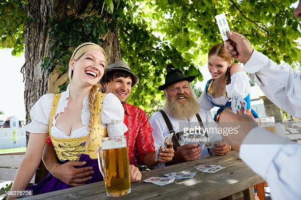 Germany, Bavaria, Upper Bavaria, Group of friends playing cards in beer garden