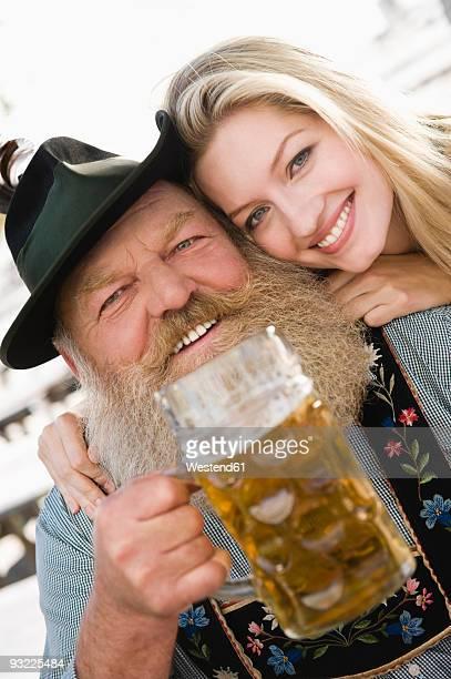 Germany, Bavaria, Upper Bavaria, senior man and young woman holding beer mug, smiling, portrait, close-up