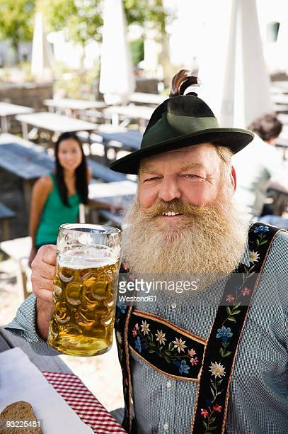 Germany, Bavaria, Upper Bavaria, Senior man in beer garden holding beer stein, portrait