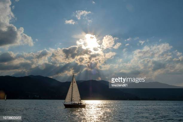 Germany, Bavaria, Upper Bavaria, Tegernsee valley, lake Tegernsee, Bad Wiessee, Sailing boat at sunset, seen from peninsula Point