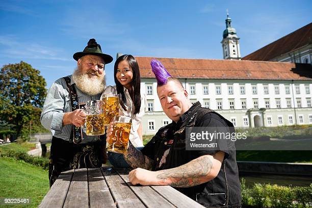 Germany, Bavaria, Upper Bavaria, two men and woman holding beer steins in beer garden, smiling, portrait
