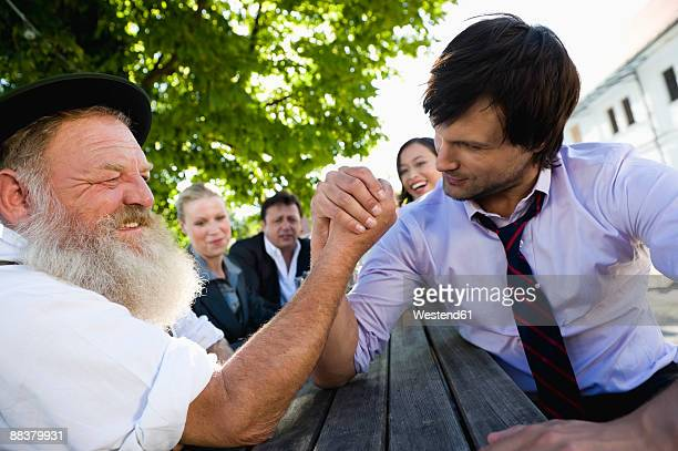 Germany, Bavaria, Upper Bavaria, Two men arm wrestling in beer garden, friends in background