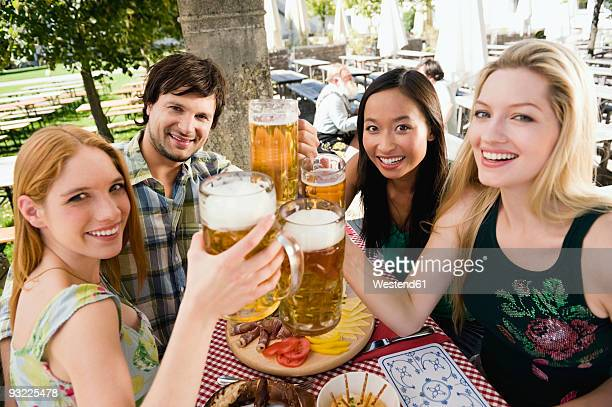 germany, bavaria, upper bavaria, young people in beer garden, smiling - beer stein stock photos and pictures