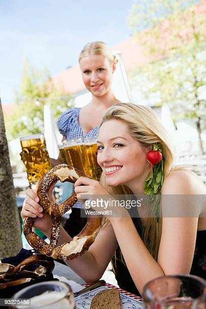 Germany, Bavaria, Upper Bavaria, Young woman in beer garden holding pretzel, portrait