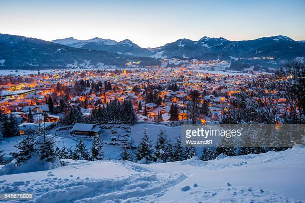 Germany, Bavaria, view to snow-covered lighted Oberstdorf in front of the Allgaeu Alps