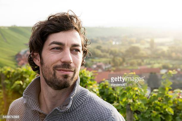 Germany, Bavaria, Volkach, portrait of winegrower in vineyard