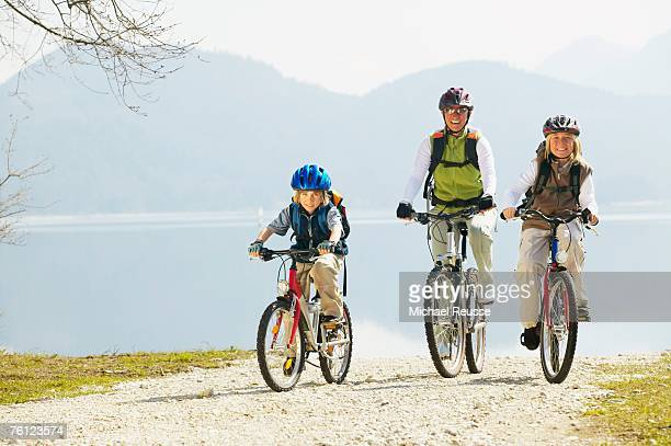Germany, Bavaria, Walchensee lake, father and children (6-9) on mountain bikes, smiling