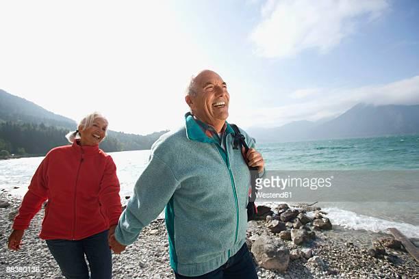 germany, bavaria, walchensee, senior couple hiking on lakeshore - seeufer stock-fotos und bilder