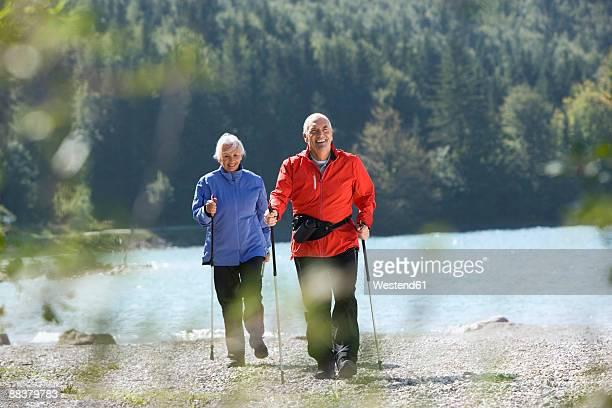 Germany, Bavaria, Walchensee, Senior couple nordic walking on lakeshore