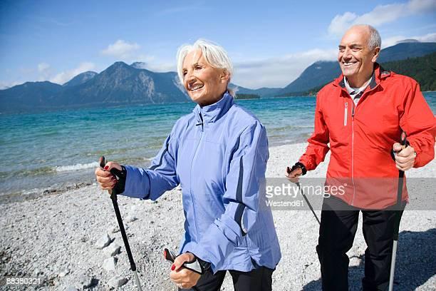 Germany, Bavaria, Walchensee, Senior couple nordic walking on lakeshore, smiling