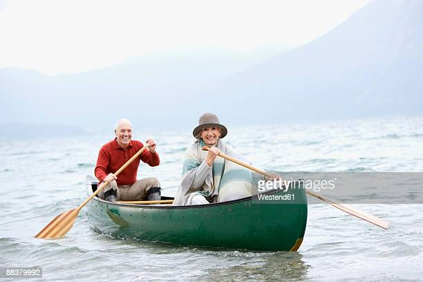 Germany, Bavaria, Walchensee, Senior couple rowing boat on lake, portrait, smiling