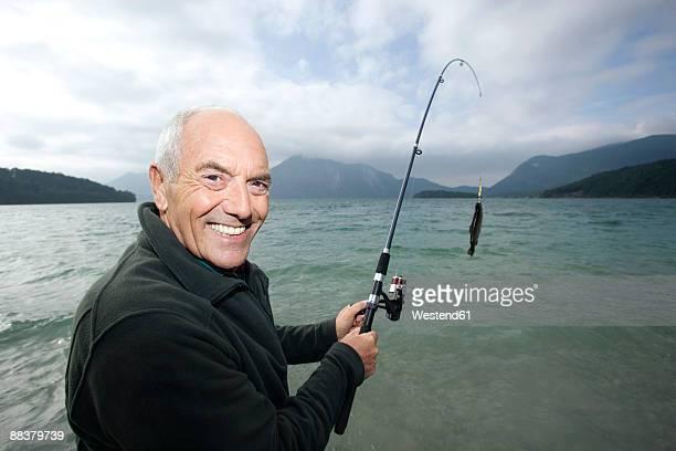 Germany, Bavaria, Walchensee, Senior man fishing in lake, smiling, close-up, portrait