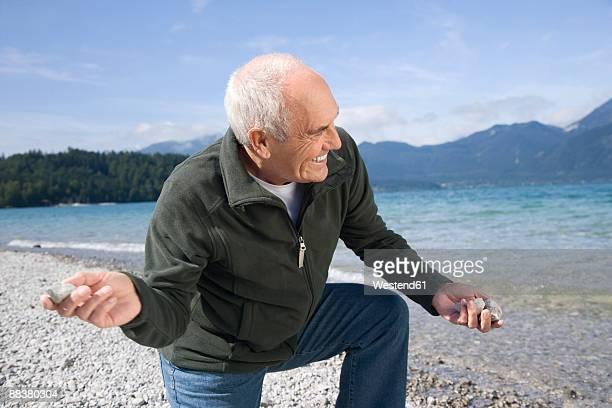 Germany, Bavaria, Walchensee, Senior man skimming stone into lake, side view