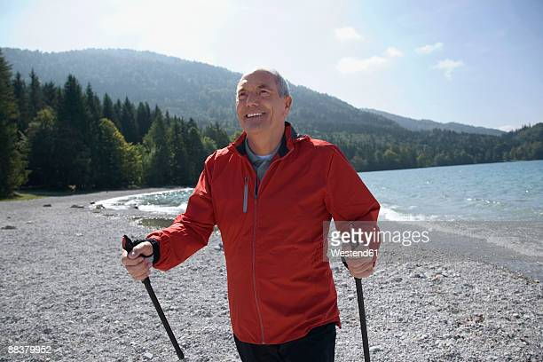 germany, bavaria, walchensee, senior man with nordic walking poles, smiling - northern european descent stock pictures, royalty-free photos & images
