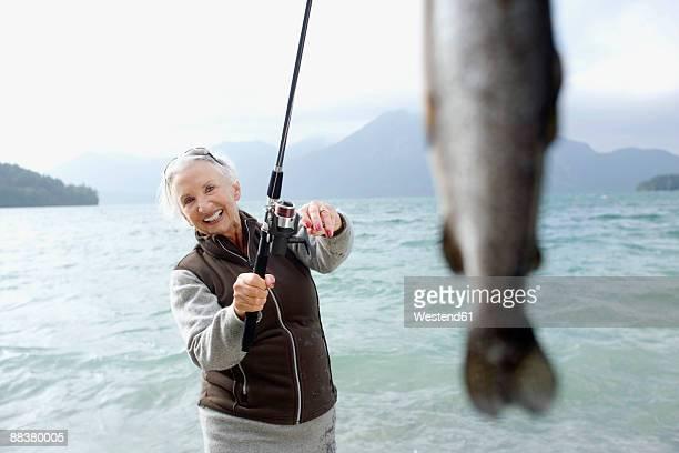 Germany, Bavaria, Walchsensee, Senior woman fishing in lake, smiling, portrait