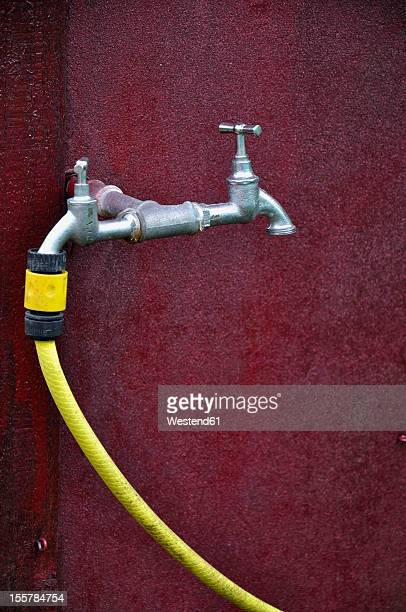 Germany, Bavaria, Water tap with yellow garden hose