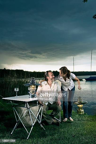 Germany, Bavaria, Woerthsee, Couple with lantrern near lakeshore while camping at dusk