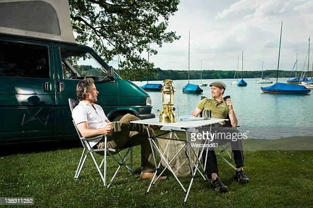 Germany, Bavaria, Woerthsee, Two men having drinks and talking near lakeshore while camping