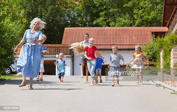 Germany, Bavaria, Woman dancing along street with group of children
