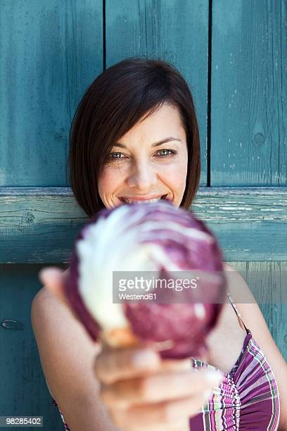 Germany, Bavaria, Mature woman holding radicchio, close-up, portrait