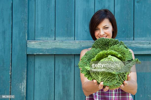 germany, bavaria, woman holding savoy cabbage, smiling, portrait - kool kool familie stockfoto's en -beelden