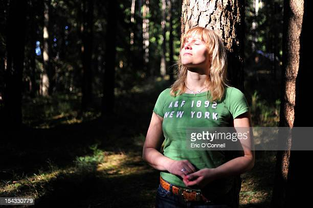 Germany, Bavaria, Woman leaning against tree with eyes closed in forest