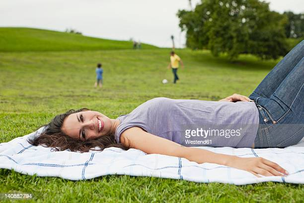 Germany, Bavaria, Woman lying on blanket, father and son playing soccer in park, smiling