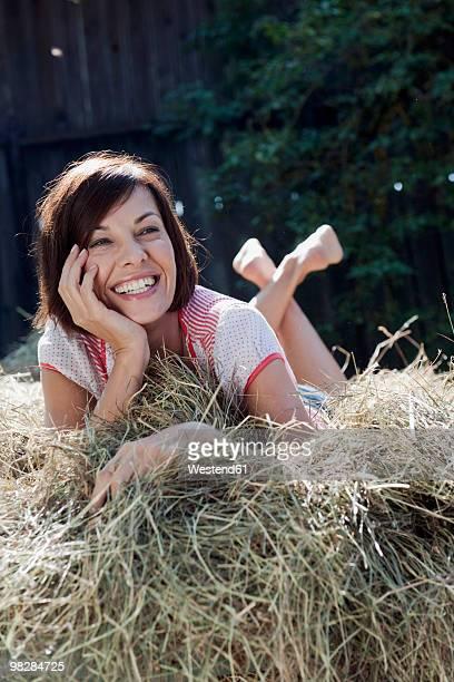 Germany, Bavaria, Woman lying on haystack, smiling, portrait